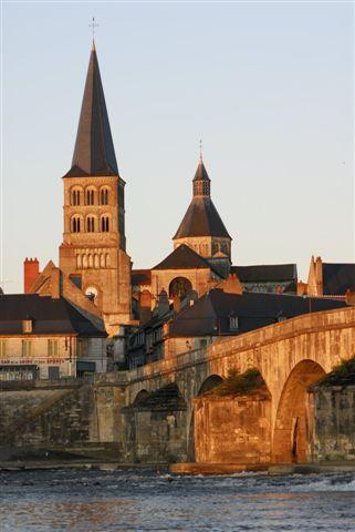 Le clocher de l'église prieurale vue du faubourg au coucher du Soleil